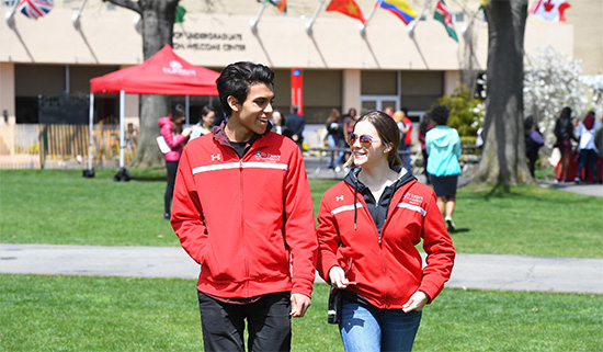 Male and femaie students walking on Great Lawn, Queens campus